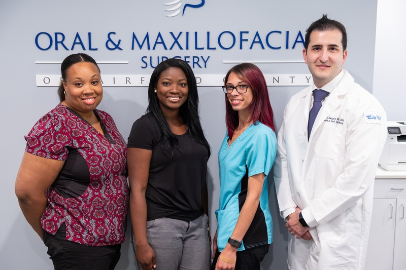 oral and maxillofacial surgery staff of four, smiling in front the office logo